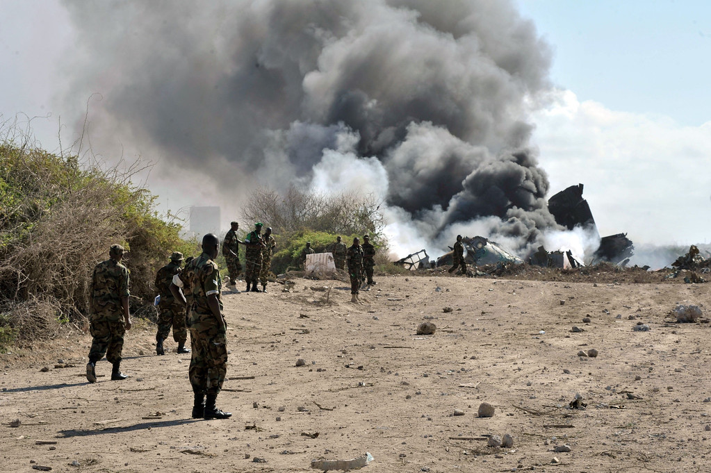 . AMISOM soldiers watch as a plane burns on the runway in Mogadishu,  on August 9, 2013. An Ethiopian Air Force aircraft crashed upon landing this morning at Mogadishu\'s Aden Adde International Airport. Two of the six crew members survived the crash. AU UN IST PHOTO / TOBIN  JONES/AFP/Getty Images