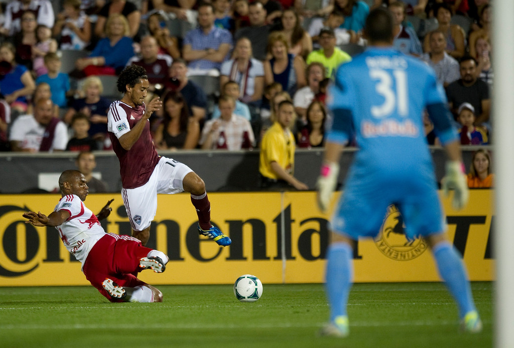 . DENVER - JULY 4: Tony Cascio, #14 of the Colorado Rapids, makes an attempt on the goal against #4 of the New York Red Bulls Jamison Olave during the second half of a MLS soccer match against the New York Red Bulls on July 4, 2013 at Dick\'s Sporting Goods Park. The Rapids defeated the Red Bulls 2-0.(Photo By Grant Hindsley / The Denver Post)