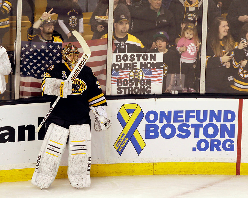 . Boston Bruins goalie Anton Khudobin (35) pauses during warm ups before an NHL hockey game against the Pittsburgh Penguins, Saturday, April 20, 2013, in Boston. A fan holds up a sign of support for the city in the background, (AP Photo/Mary Schwalm)