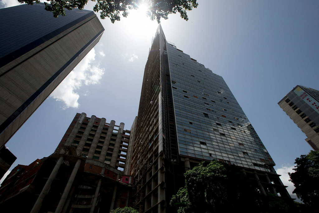 . A view of the Tower of David, a building that was abandoned in the 1990s and became the worldís tallest slum, the half-built skyscraper was transformed by squatters into a vertical ghetto, in Caracas, Venezuela, Tuesday, July 22, 2014. Officials and armed soldiers began moving out the first of thousands of squatters who have lived for nearly a decade in a soaring, half-built skyscraper in the heart of Caracas. (AP Photo/Fernando Llano)