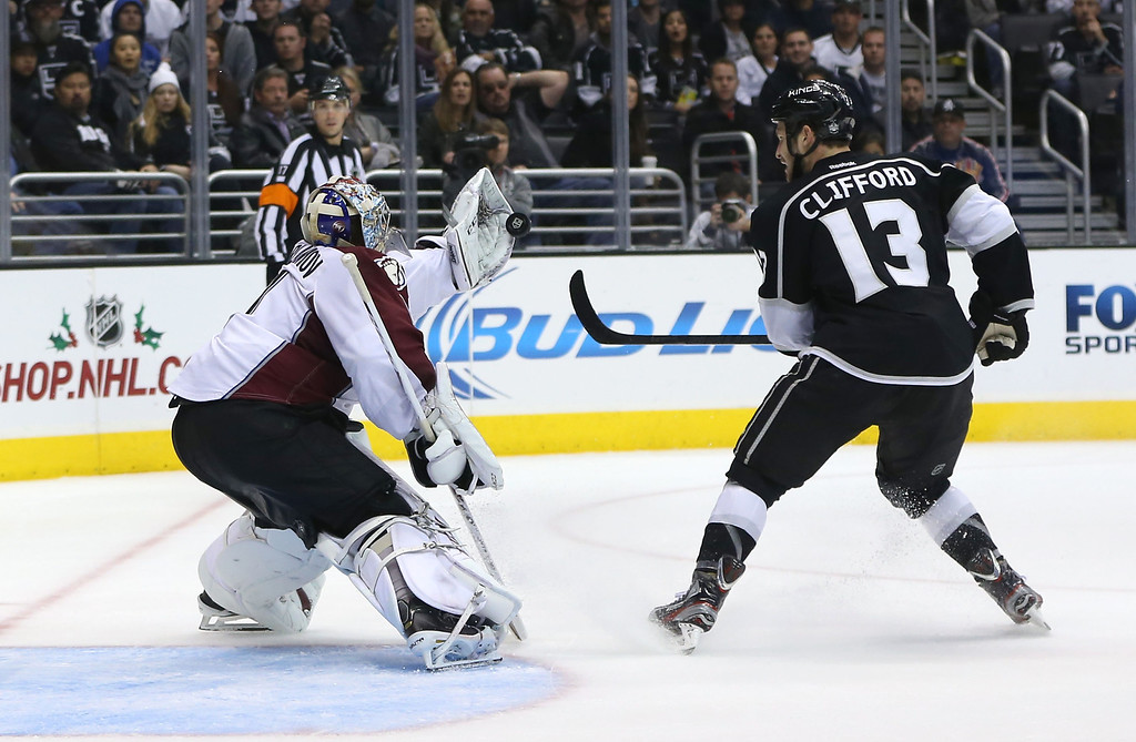 . LOS ANGELES, CA - NOVEMBER 23:  Kyle Clifford #13 of the Los Angeles Kings deflects the puck into the glove of goaltender Semyon Varlamov #1 of the Colorado Avalanche in the second period during the NHL game at Staples Center on November 23, 2013 in Los Angeles, California. The Avalanche defeated the Kings 1-0 in overtime. (Photo by Victor Decolongon/Getty Images)
