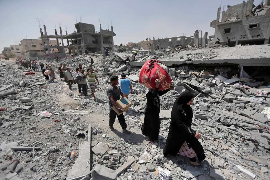 . Palestinians carry their belongings after salvaging them from their destroyed houses in the heavily bombed town of Beit Hanoun, Gaza Strip, close to the Israeli border, Friday, Aug. 1, 2014. A three-day Gaza cease-fire that began Friday quickly unraveled, with Israel and Hamas accusing each other of violating the truce. (AP Photo/Lefteris Pitarakis)