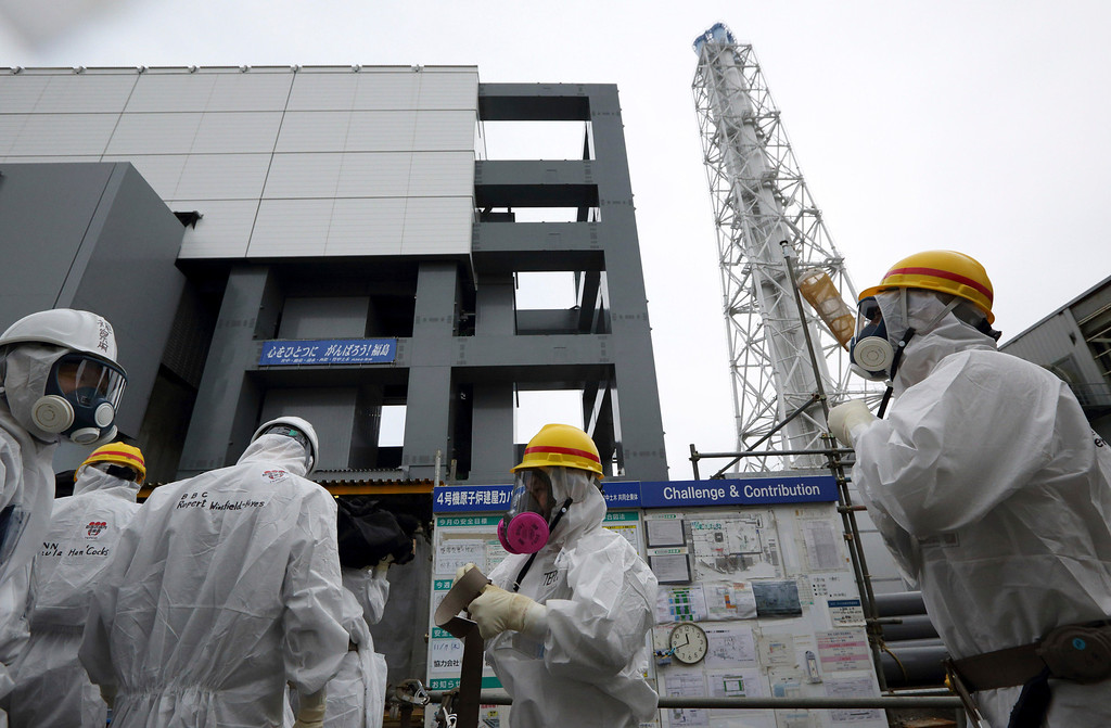 . Members of the media and Tokyo Electric Power Co. employees wearing protective suits and masks stand outside the Unit 4 reactor before starting their inspection at the Fukushima Dai-ichi nuclear power plant in Okuma, Fukushima, northeastern Japan, Thursday, Nov. 7, 2013.  (AP Photo/Tomohiro Ohsumi, Pool)