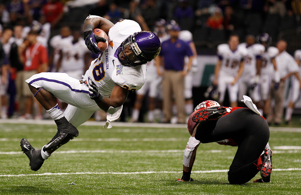 . East Carolina running back Reggie Bullock (28) tumbles into the endzone on a touchdown run in the second half of the New Orleans Bowl, an NCAA college football game in New Orleans, Saturday, Dec. 22, 2012. Louisiana-Lafayette beat East Carolina 43-34. At right is Louisiana-Lafayette safety Rodney Gillis (21). (AP Photo/Bill Haber)
