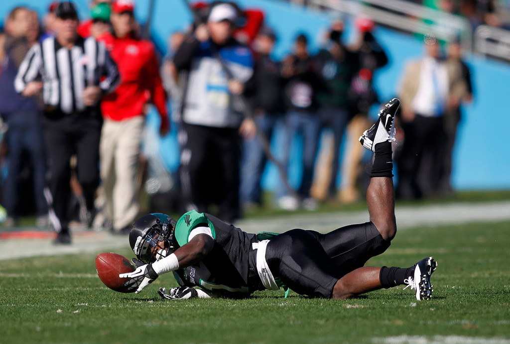. North Texas defensive back Zed Evans (1) recovers a fumble by UNLV punt returner Keith Whitely during the first half of the Heart of Dallas NCAA college football game, Wednesday, Jan. 1, 2014, in Dallas. (AP Photo/Mike Stone)
