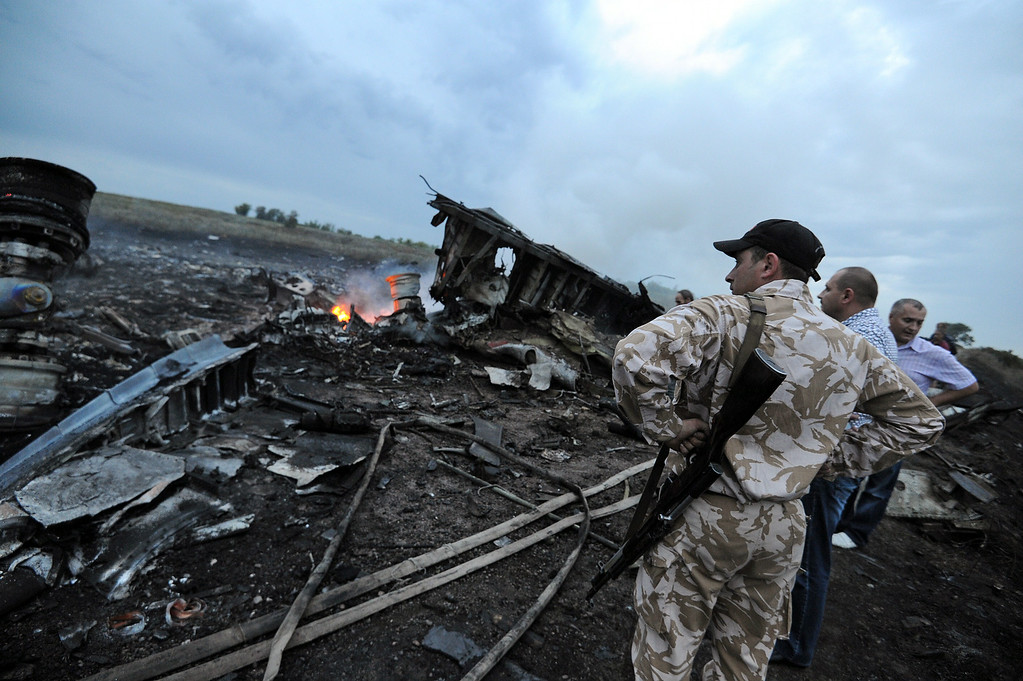 . People stand next to the wreckages of the malaysian airliner carrying 295 people from Amsterdam to Kuala Lumpur after it crashed, near the town of Shaktarsk, in rebel-held east Ukraine, on July 17, 2014. Pro-Russian rebels fighting central Kiev authorities claimed on Thursday that the Malaysian airline that crashed in Ukraine had been shot down by a Ukrainian jet. AFP PHOTO/DOMINIQUE  FAGET/AFP/Getty Images