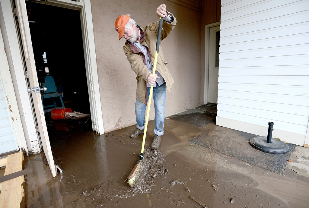 . Howard Palmer sweeps muddy water from his workshop after flood waters ran through heavy rains in Boulder, Colorado September 13, 2013. BOULDER DAILY CAMERA/ Mark Leffingwell