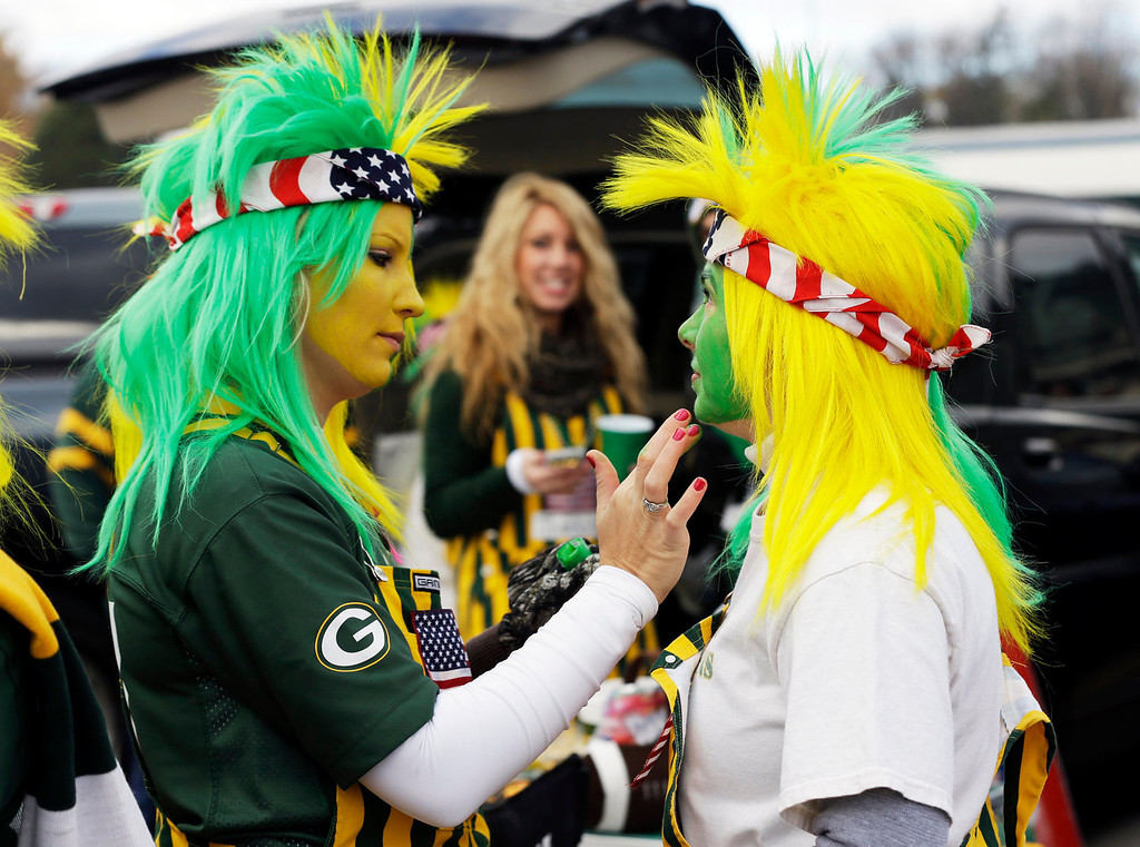 . Mell Whitehouse puts makeup on Carrie Hyland before an NFL football game between the Green Bay Packers and the Philadelphia Eagles Sunday, Nov. 10, 2013, in Green Bay, Wis. (AP Photo/Mike Roemer)
