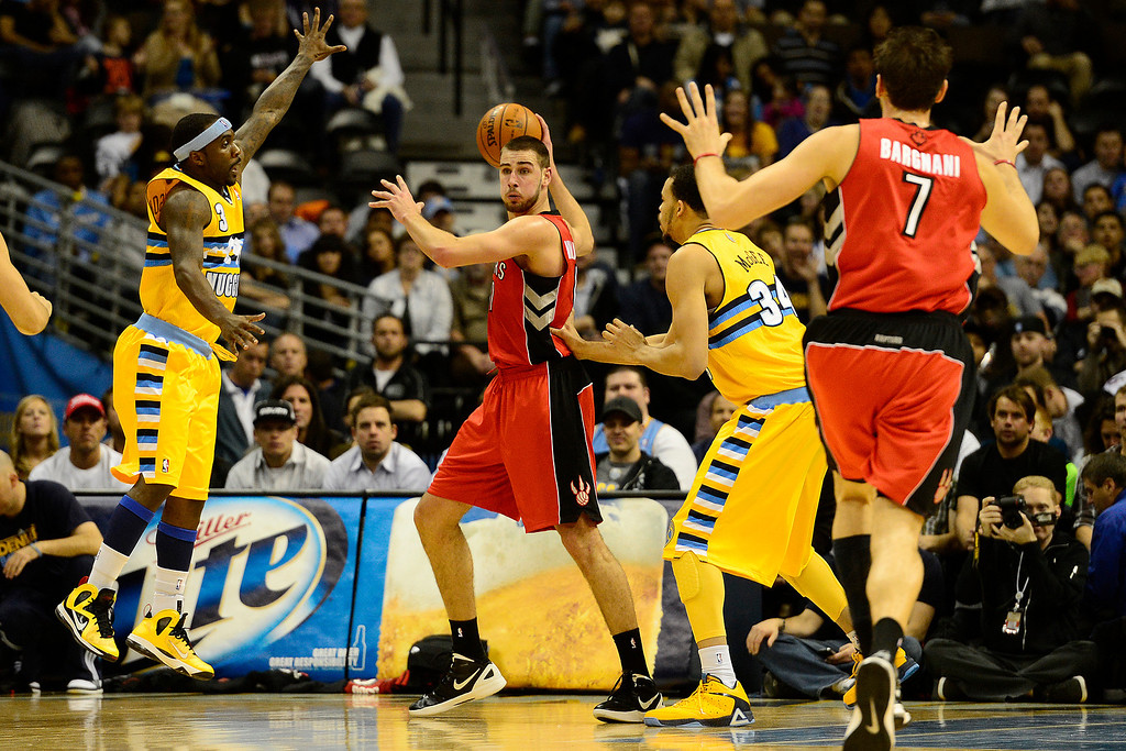 . Toronto Raptors small forward Linas Kleiza (11) is pressured by Denver Nuggets point guard Ty Lawson (3) and center JaVale McGee (34) during the first half at the Pepsi Center on Monday, December 3, 2012. AAron Ontiveroz, The Denver Post