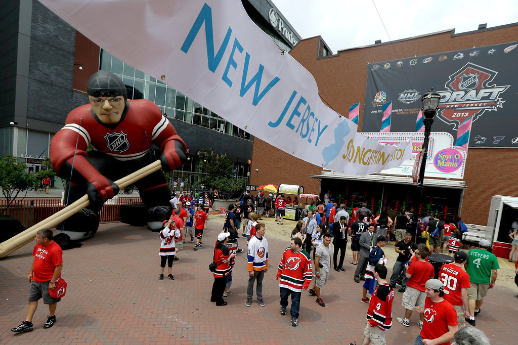 . A crowd gathers outside of Prudential Center during an event hosted before the start of the NHL hockey draft, Sunday, June 30, 2013, in Newark, N.J. (AP Photo/Julio Cortez)