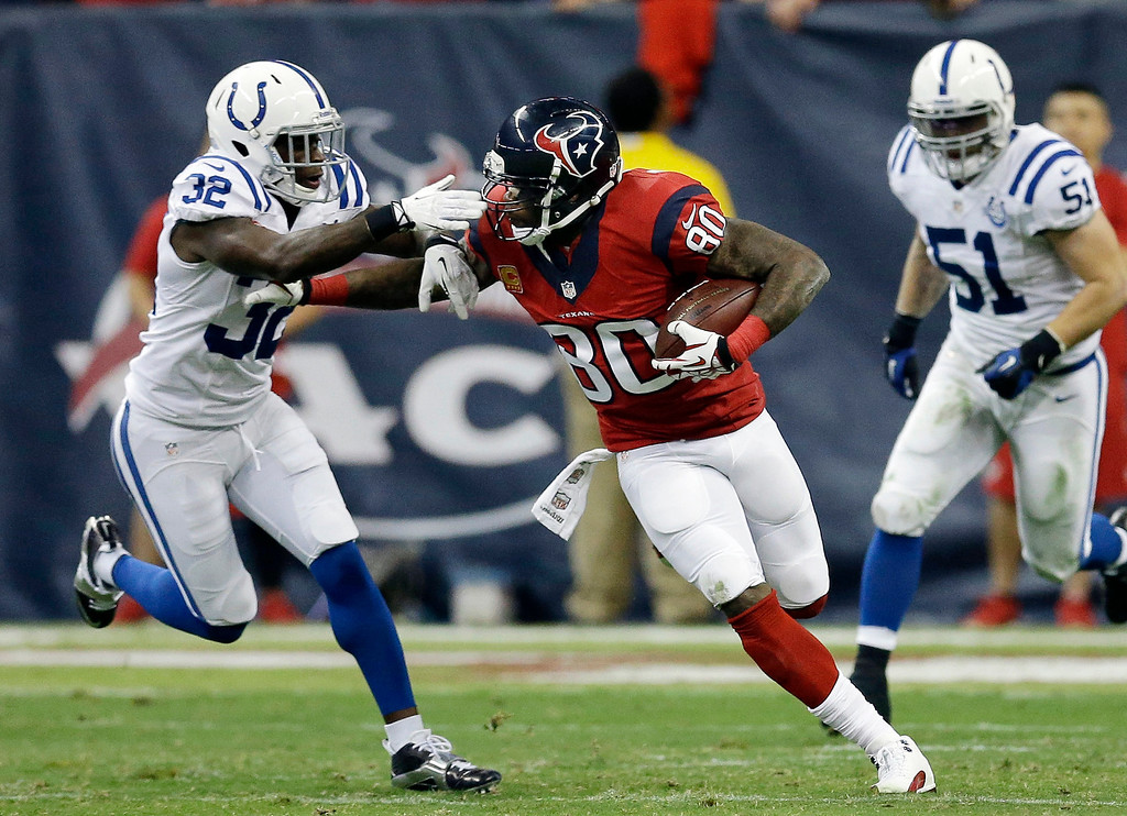 . Houston Texans\' Andre Johnson (80) fends off Indianapolis Colts\' Cassius Vaughn (32) after making a catch during the first quarter of an NFL football game Sunday, Nov. 3, 2013, in Houston. (AP Photo/David J. Phillip)
