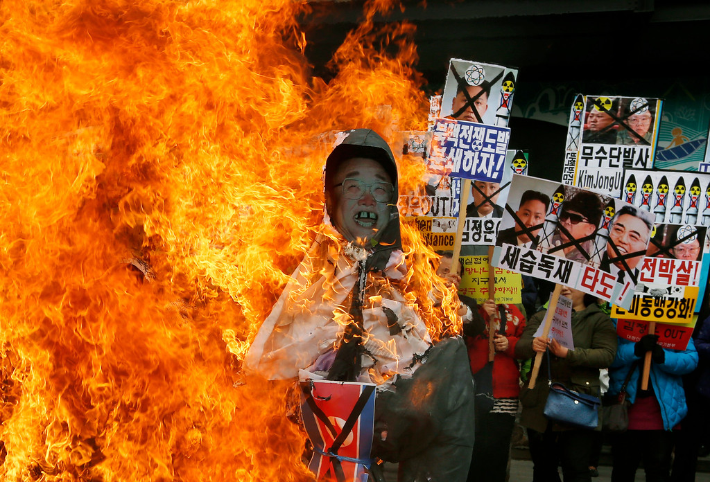 """. South Korean protesters burn effigies of North Korean leader Kim Jong-Un, and late leaders Kim Jong Il and Kim Il Sung at an anti-North Korea protest on the birthday of Kim Il Sung in Seoul, South Korea Monday, April 15, 2013. South Korea\'s defense minister, Kim Kwan-jin, told a parliamentary committee in Seoul on Monday that North Korea remains ready to launch a missile from its east coast, though he declined to disclose how he got the information. The sign at center showing images of the Kim family reads \""""Throw Them Out.\""""  (AP Photo/Kin Cheung)"""
