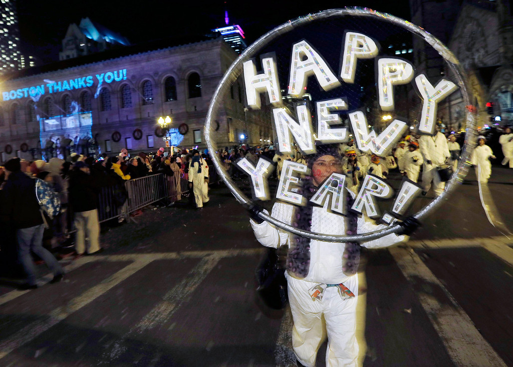 . Marchers make their way down Boylston Street during a parade as part of New Year\'s Eve celebrations in Boston, Tuesday, Dec. 31, 2013. (AP Photo/Michael Dwyer)