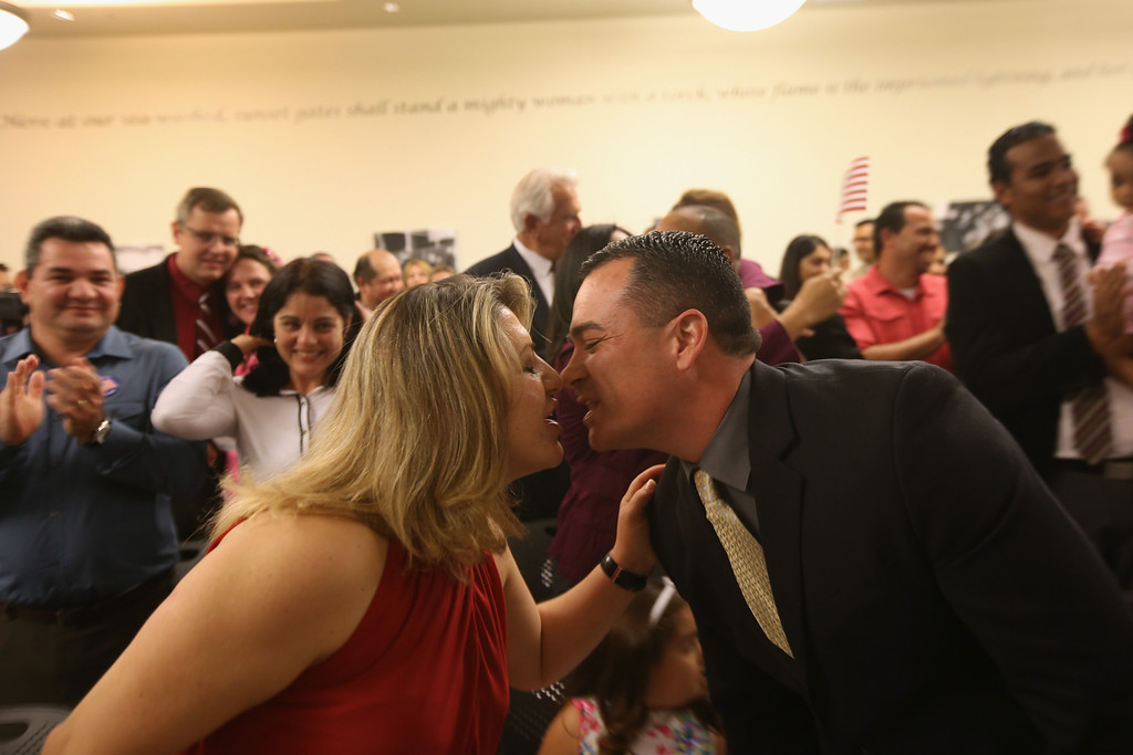 . Fabricia and Wagner Darosa kiss after becoming American citizens at a special Valentine\'s Day naturalization ceremony for married couples on February 14, 2013 in Tampa, Florida. The U.S. Citizenship and Immigration Service (USCIS) held the Valentine\'s Day ceremony in their Tampa office for 28 married couples from 15 different countries.  (Photo by John Moore/Getty Images)