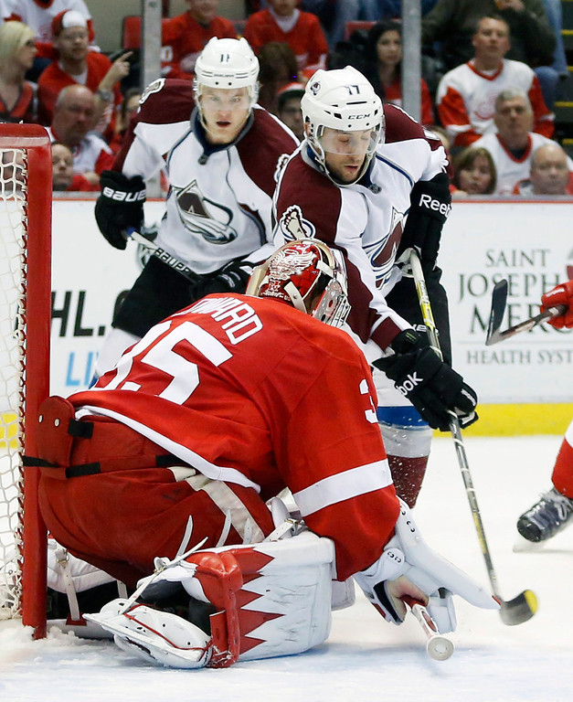 . Colorado Avalanche right wing Aaron Palushaj, right, tries to get a shot against Detroit Red Wings goalie Jimmy Howard (35) as Colorado Avalanche left wing Jamie McGinn, left, watches in the first period of an NHL hockey game Monday, April 1, 2013, in Detroit. (AP Photo/Duane Burleson)