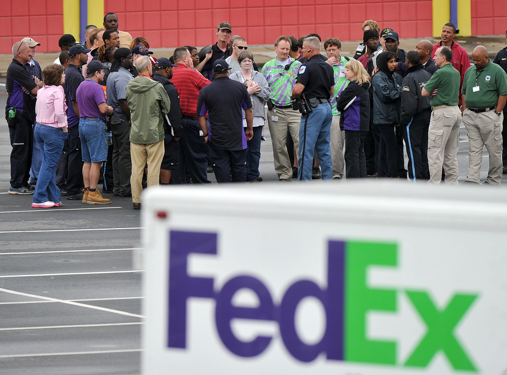 . A Cobb County Police Officer speaks to FedEx employees and family members gathered at the parking lot of a skating rink located near the shipping facility where a gunman open fire in Kennesaw, Ga., on Tuesday, April 29, 2014.   (AP Photo/Atlanta Journal-Constitution, Brant Sanderlin)