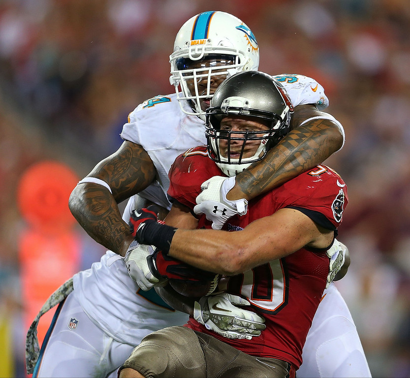 . Brian Leonard #30 of the Tampa Bay Buccaneers is tackled by Randy Starks #94 of the Miami Dolphins during a game at Raymond James Stadium on November 11, 2013 in Tampa, Florida.  (Photo by Mike Ehrmann/Getty Images)