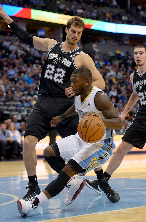 . DENVER, CO - OCTOBER 14: San Antonio Spurs power forward Tiago Splitter (22) stops Denver Nuggets point guard Nate Robinson (10) from driving to the basket October 14, 2013 at Pepsi Center. (Photo By John Leyba/The Denver Post)