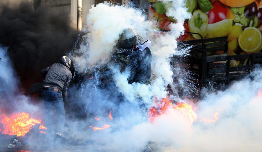 . Anti-government protester throw tires in a barricade on the streets of Kievin downtown Kiev, Ukraine, 18 February 2014.  EPA/IGOR KOVALENKO