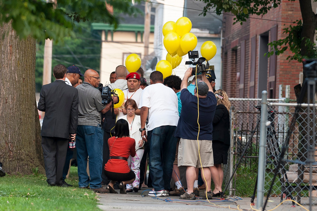 . Michelle Knight talks (C) with reporters on August 7, 2013 outside the home of Ariel Castro in Cleveland, Ohio.  (Photo by Angelo Merendino/Getty Images)