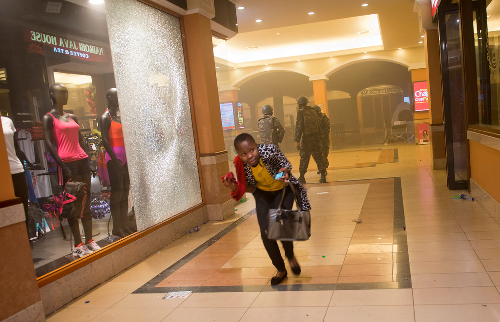 . A woman who had been hiding during the gun battle runs for cover after armed police, seen behind, enter the Westgate Mall in Nairobi, Kenya, Saturday, Sept. 21, 2013.  (AP Photo/Jonathan Kalan)