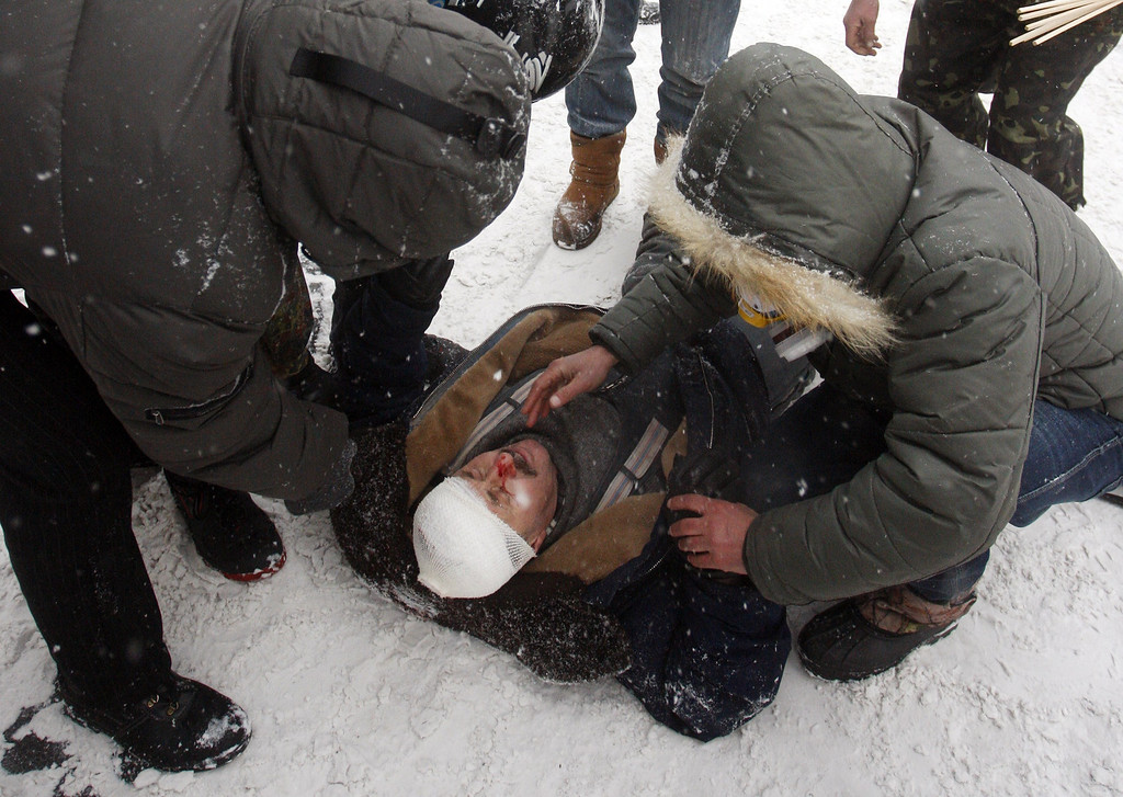 . People assist a wounded demonstrator during clashes between protestors and police in the centre of Kiev on January 22, 2014.  AFP PHOTO/ YURIY KIRNICHNY/AFP/Getty Images