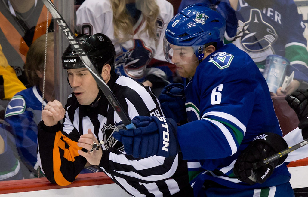 . Vancouver Canucks\' Yannick Weber, right, of Switzerland, runs into referee Ian Walsh during the third period of an NHL hockey game against the Colorado Avalanche on Thursday, April 10, 2014, in Vancouver, British Columbia. (AP Photo/The Canadian Press, Darryl Dyck)
