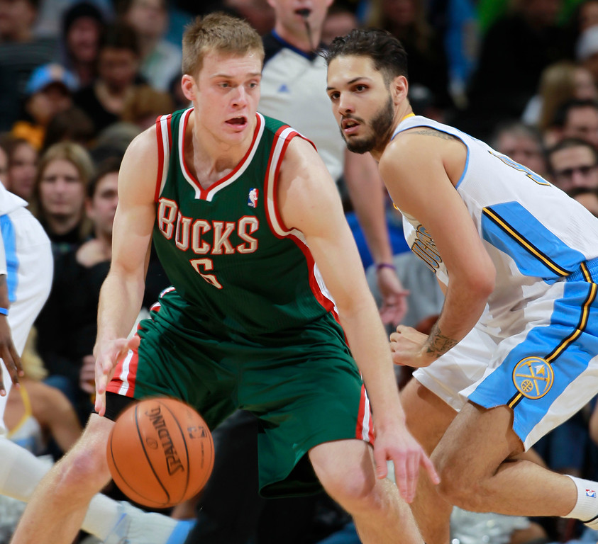 . Milwaukee Bucks guard Nate Wolters, front, works ball inside against Denver Nuggets guard Evan Fournier, of France, in the fourth quarter of the Nuggets\' 110-100 victory in an NBA basketball game in Denver on Wednesday, Feb. 5, 2014. (AP Photo/David Zalubowski)