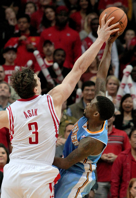 . Houston Rockets center Omer Asik (3) blocks the shot of Denver Nuggets guard Aaron Brooks during overtime of an NBA basketball game in Houston on Sunday, April 6, 2014. The Rockets won 130-125.   (AP Photo/Richard Carson)