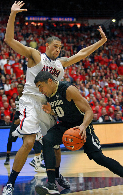 . Colorado\'s Josh Scott (40) drives into the pressing defense of Arizona\'s Brandon Ashley, left, in the second half of an NCAA college basketball game on Thursday, Jan. 23, 2014 in Tucson, Ariz. (AP Photo/John Miller)