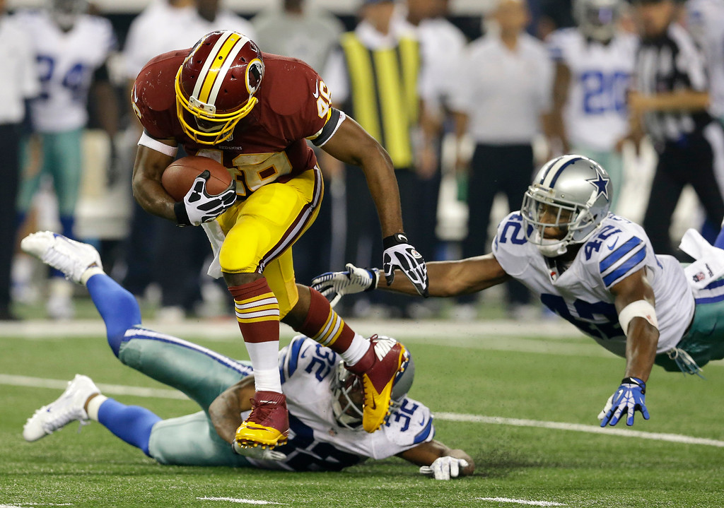 . Washington Redskins running back Alfred Morris (46) escapes tackles by Dallas Cowboys\' Orlando Scandrick (32) and Barry Church (42) as Morris heads to the end zone for a touchdown in the second half of an NFL football game, Sunday, Oct. 13, 2013, in Arlington, Texas. (AP Photo/LM Otero)