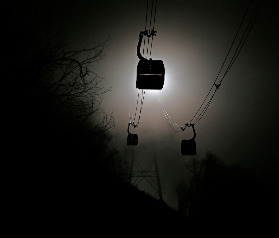 . Gondolas are shrouded in fog as the travel between between biathlon and cross country skiing venues and the community below at the Sochi 2014 Winter Olympics, Sunday, Feb. 16, 2014, in Krasnaya Polyana, Russia. (AP Photo/Charlie Riedel)