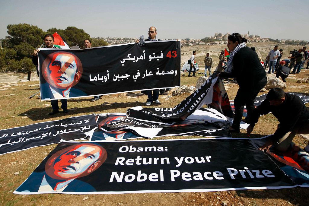 ". Palestinian activists organise banners depicting U.S. President Barack Obama at a protest camp in an area known as ""E1\"", which connects the two parts of the Israeli-occupied West Bank outside Arab suburbs of East Jerusalem March 20, 2013. Palestinian activists set up the protest camp on Wednesday close to where Israel wants to build a new settlement, drawing attention to their struggle for land during a visit to the region by Obama. REUTERS/Ammar Awad"