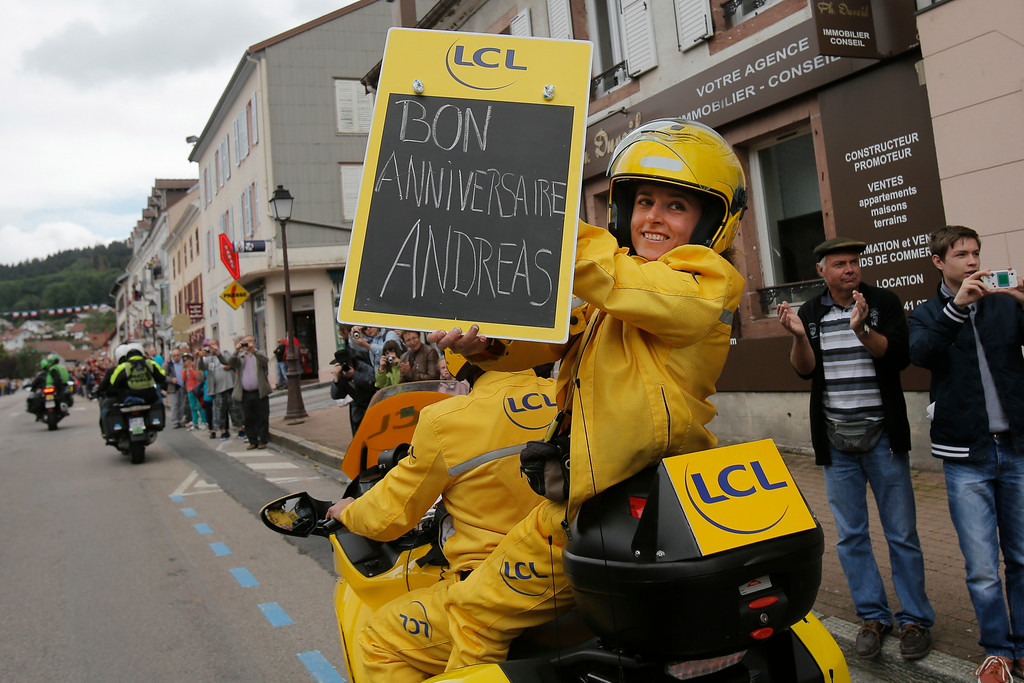 . The official timekeeper holds a message on a blackboard for Germany\'s Andreas Schillinger wishing him a happy birthday as he cycles in the pack during the ninth stage of the Tour de France cycling race over 170 kilometers (105.6 miles) with start in Gerardmer and finish in Mulhouse, France, Sunday, July 13, 2014. (AP Photo/Christophe Ena)