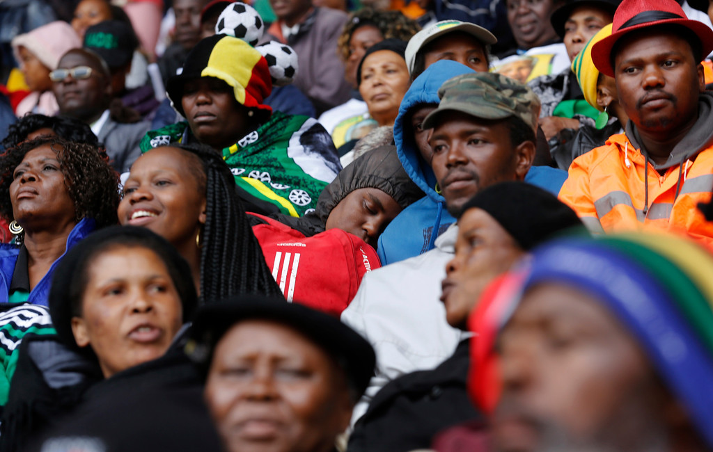 . A mourner sleeps during the memorial service for former South African president Nelson Mandela at the FNB Stadium in Soweto near Johannesburg, Tuesday, Dec. 10, 2013. (AP Photo/Markus Schreiber)