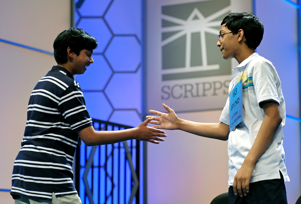 . Scripps National Spelling Bee champion Arvind Mahankali, 13, of Bayside Hills, N.Y. extends his hand to second place finisher Pranav Sivakumar, 13, Tower Lakes, Ill., after Sivakumar incorrectly spelled his final word during the finals in Oxon Hill, Md., Thursday, May 30, 2013. (AP Photo/Cliff Owen)