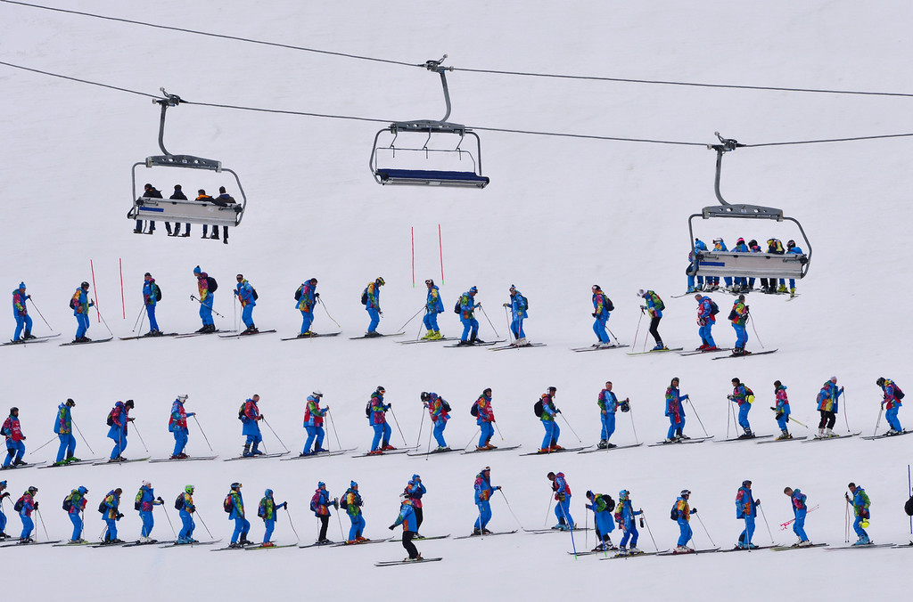 . Volunteers flatten the snow prior to the start of the Men\'s Alpine Skiing Super Combined Slalom at the Rosa Khutor Alpine Center during the Sochi Winter Olympics on February 14, 2014.  DIMITAR DILKOFF/AFP/Getty Images