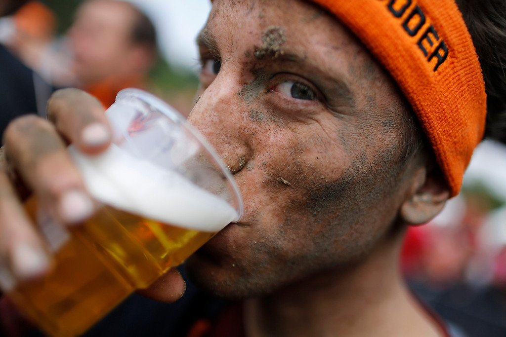 """. A participant of the \""""Tough Mudder\"""" endurance event series drinks a beer after crossing the finish line in the Fursten Forest, a former British Army training ground near the north-western German city of Osnabrueck July 13, 2013. The hardcore but un-timed event over 16 km (10 miles) was designed by British Special Forces to test mental as well as physical strength. Some 4,000 competitors had to overcome obstacles of common human fears, such as fire, water, electricity and heights.   REUTERS/Wolfgang Rattay"""