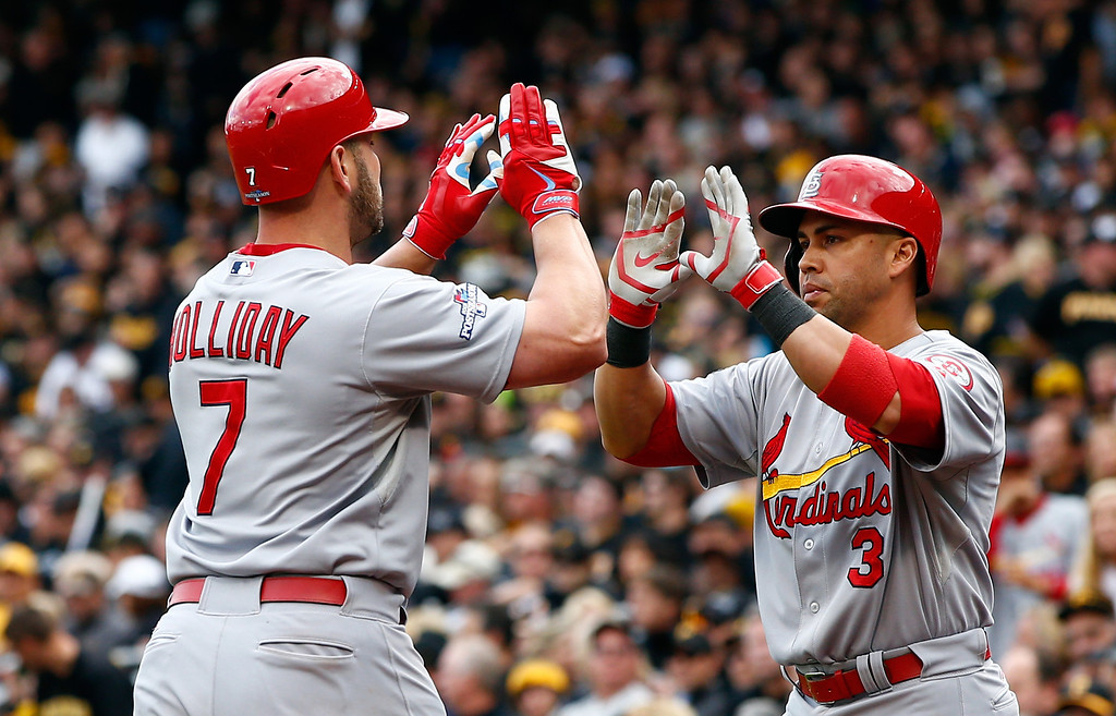 . Matt Holliday #7 of the St. Louis Cardinals celebrates scoring a two run home run with teammates Carlos Beltran #3 against Charlie Morton #50 of the Pittsburgh Pirates in the sixth inning during Game Four of the National League Division Series at PNC Park on October 7, 2013 in Pittsburgh, Pennsylvania.  (Photo by Jared Wickerham/Getty Images)