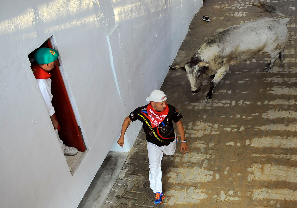 . A reveler flees from a bull during the fifth run of the famed San Fermin festival, in Pamplona northern Spain on Thursday, July 11, 2013. One person has been hospitalized after several thousand people tested their speed and bravery by dashing with six fighting bulls through the streets of the northern Spanish city of Pamplona. (AP Photo/Alvaro Barrientos)