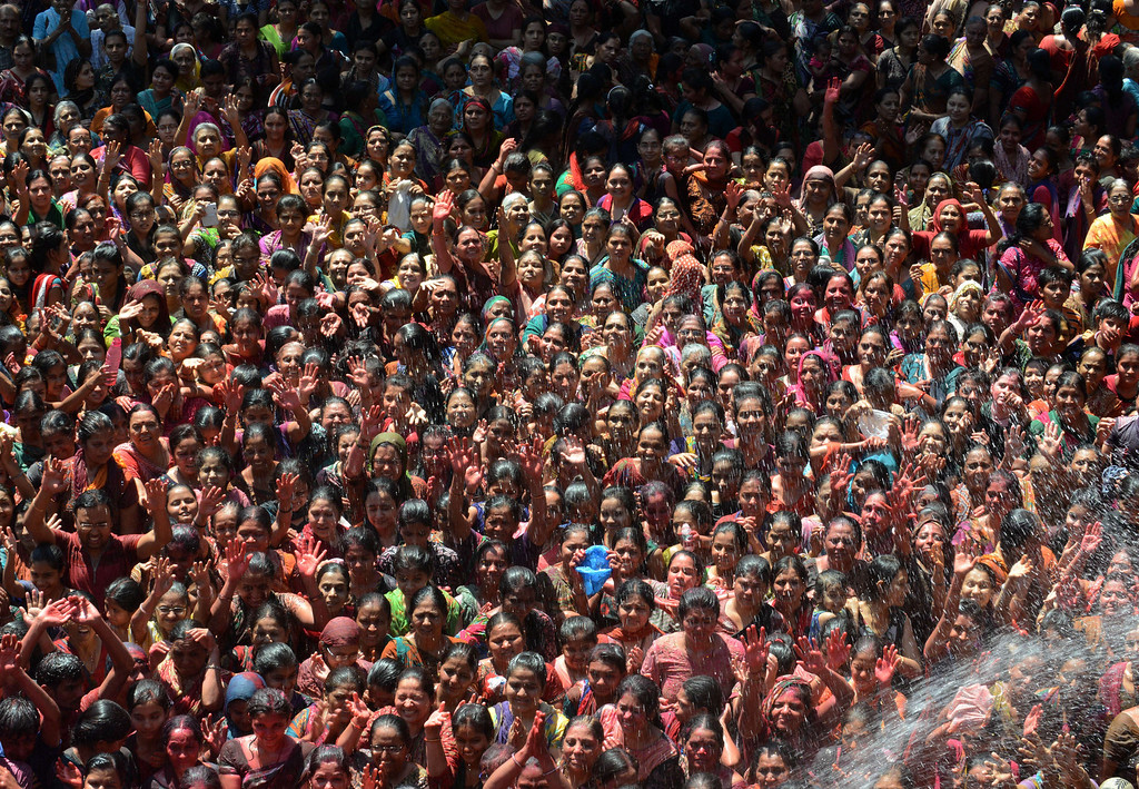 . Indian Hindu devotees are sprayed with water and colored powder as they celebrate the Holi festival at the Swaminarayan Temple at Kalupur in Ahmedabad on March 17, 2014. Holi, also called the Festival of Colors, is a popular Hindu spring festival observed in India at the end of the winter season on the last full moon day of the lunar month.  AFP PHOTO / Sam PANTHAKY/AFP/Getty Images