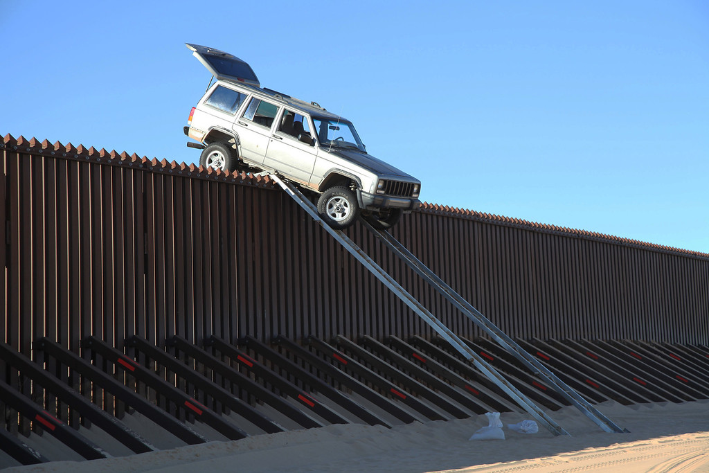 . In this photo provided by the U.S. Customs and Border Protection, a silver Jeep Cherokee that suspected smugglers were attempting to drive over the U.S.-Mexico border fence is stuck at the top of a makeshift ramp early Wednesday, Oct. 31, 2012 near Yuma, Ariz. U.S. Border Patrol agents from the Yuma Station seized both the ramps and the vehicle, which stalled at the top of the ramp after it became high centered. The fence is approximately 14 feet high where the would-be smugglers attempted to illegally drive across the border. The two suspects fled into Mexico when the agents arrived at the scene. (AP Photo/U.S. Customs and Border Protection)