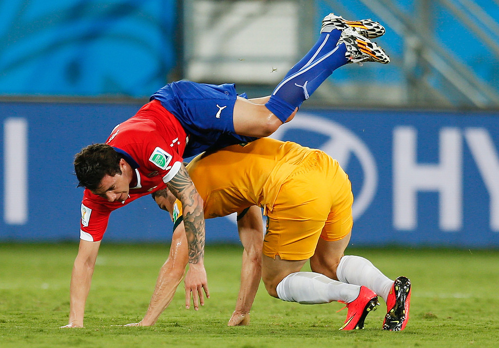 . Chile\'s Eugenio Mena, goes over the top from a challenge by Australia\'s Mathew Leckie during the group B World Cup soccer match between Chile and Australia in the Arena Pantanal in Cuiaba, Brazil, Friday, June 13, 2014.  (AP Photo/Frank Augstein)