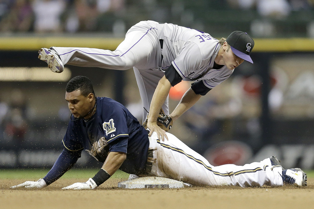 . MILWAUKEE, WI - JUNE 27: Carlos Gomez #27 of the Milwaukee Brewers steals second base in the bottom of the eighth inning against the Colorado Rockies at Miller Park on June 27, 2014 in Milwaukee, Wisconsin. (Photo by Mike McGinnis/Getty Images)