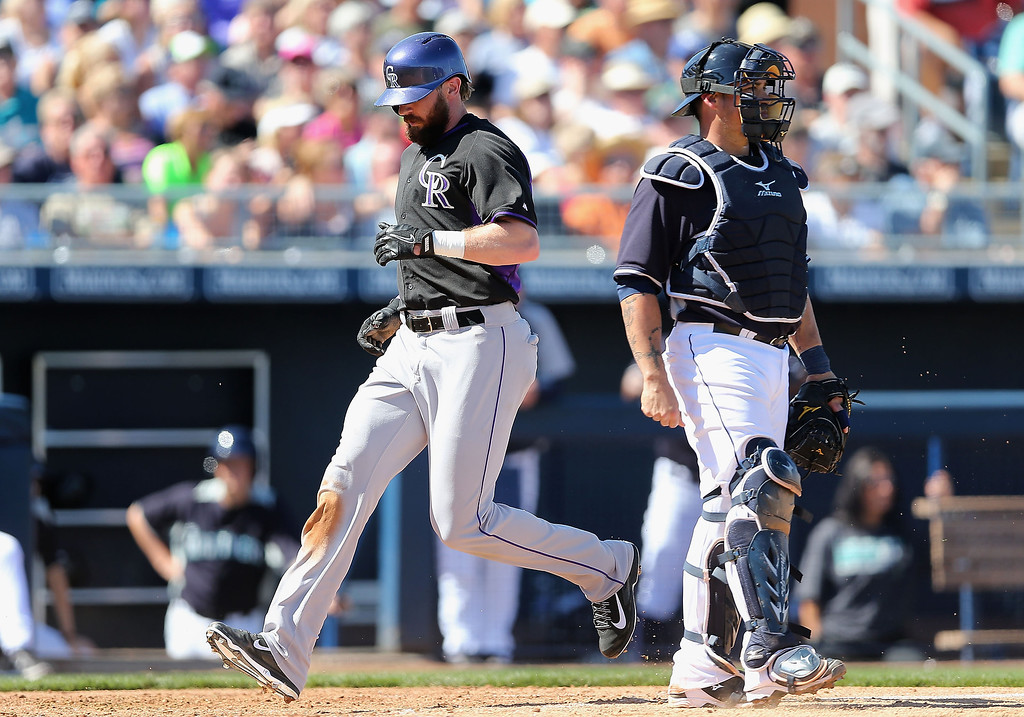 . Charlie Blackmon #19 of the Colorado Rockies scores a third inning run past catcher Humberto Quintero #35 of the Seattle Mariners during the spring training game at Peoria Stadium on March 3, 2014 in Peoria, Arizona.  (Photo by Christian Petersen/Getty Images)