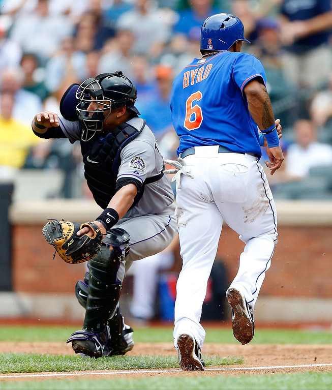 . Marlon Byrd #6 of the New York Mets tags up and scores a fourth inning run past Yorvit Torrealba #8 of the Colorado Rockies at Citi Field on August 8, 2013 in the Flushing neighborhood of the Queens borough of New York City. The Mets defeated the Rockies 2-1.  (Photo by Jim McIsaac/Getty Images)