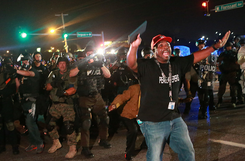. A citizen peacekeeper tries to keep protesters back as police advance Monday, Aug. 18, 2014, in Ferguson, Mo. The Aug. 9 shooting of Michael Brown by a police officer has touched off rancorous protests in Ferguson, a St. Louis suburb where police have used riot gear and tear gas. (AP Photo/St. Louis Post-Dispatch, Christian Gooden)