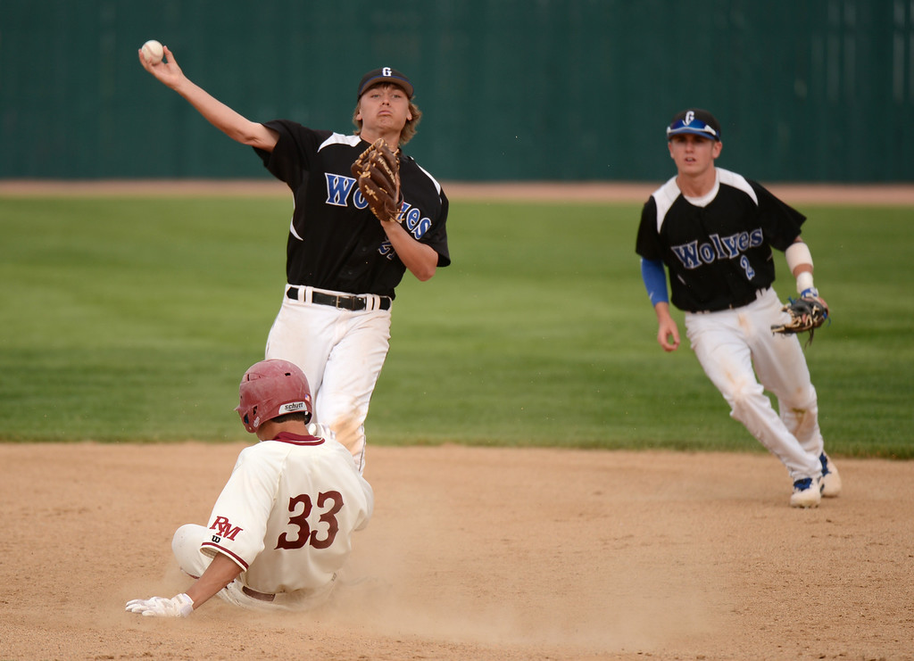 . DENVER, CO. - MAY 17 : Brook Adams of Grandview High School infielder (21) throws the ball to first base after tagging Hunter Noell of Rocky Mountain High School (33) by Jake Thurston (2), right, during the 5A playoff game at All City Field. Denver, Colorado. Grandview won 9-2. May 17, 2013. (Photo By Hyoung Chang/The Denver Post)