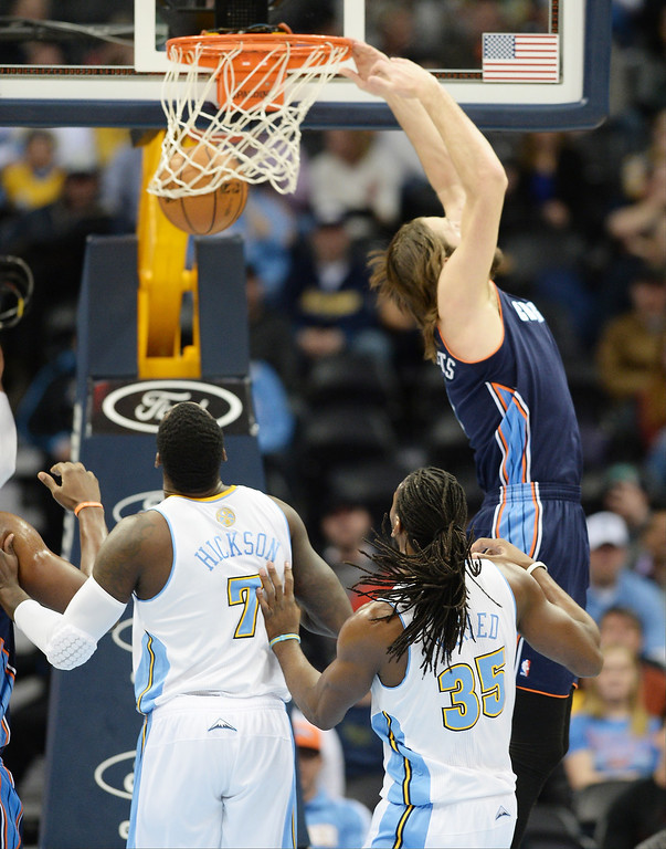 . Josh McRoberts of the Charlotte Bobcats (11), top, dunks in the first half. (Photo by Hyoung Chang/The Denver Post)