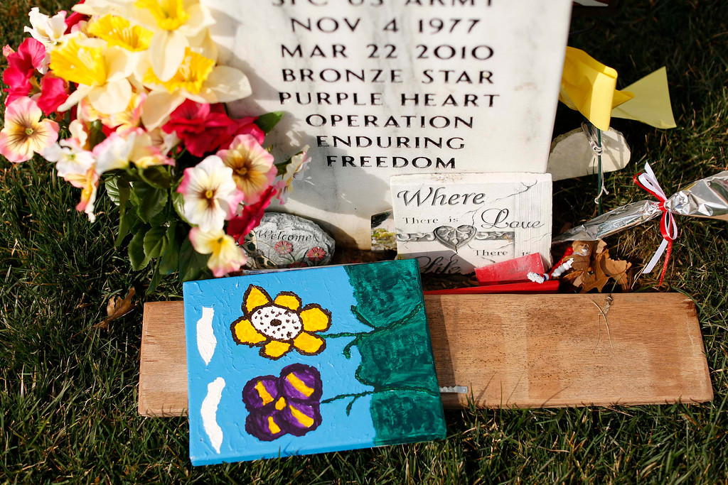 . Paintings of flowers sit beside real flowers at a grave in Section 60 at Arlington National Cemetery in Virginia, March 13, 2013. Section 60 contains graves of soldiers from the wars in Iraq and Afghanistan. Picture taken March 13, 2013. REUTERS/Kevin Lamarque